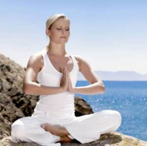 Woman in yoga peace pose by ocean