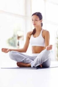 Woman in yoga pose near sunlit window
