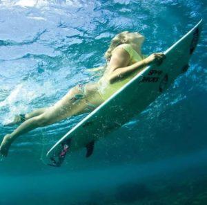 Woman surfing on surfboard in ocean