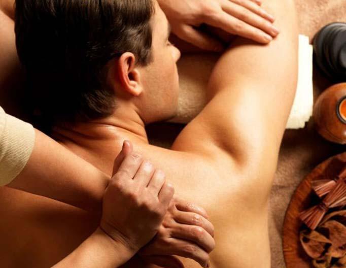 Man having a deep tissue massage with therapists hands massaging shoulder