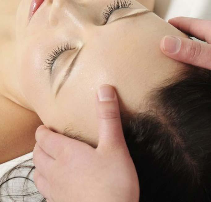 Massage therapist massaging a womans scalp