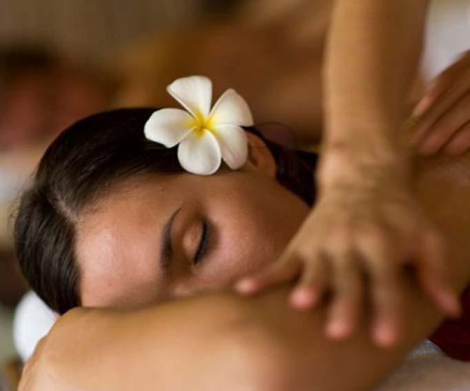 Woman enjoying a kahuna massage with frangipani flower in hair