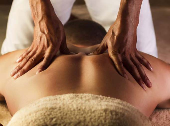 Two massage therapists hands on clients back