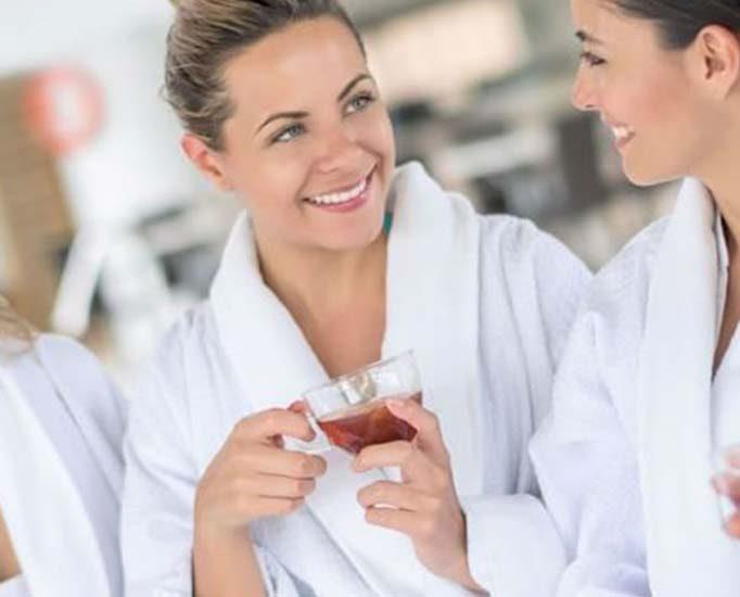 Women drinking herbal tea in massage robes