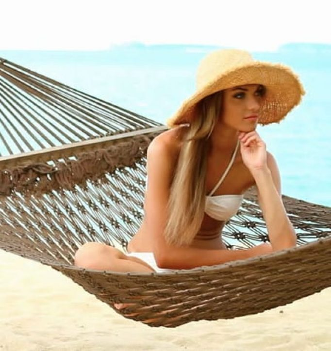 Woman sitting in hammock with hat on