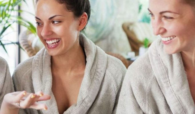 Women at a hens party pamper in spa robes