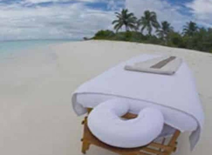 Mobile massage table on beach with white towels