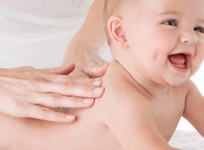 Woman massaging a babys back