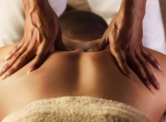 Massage therapist pressing into mans back with thumbs