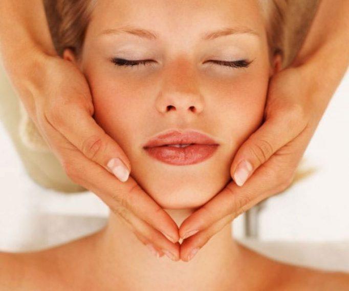 Beauty therapist giving woman a face massage